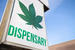 legal online cannabis dispensary sign with a large marijuana leaf on it